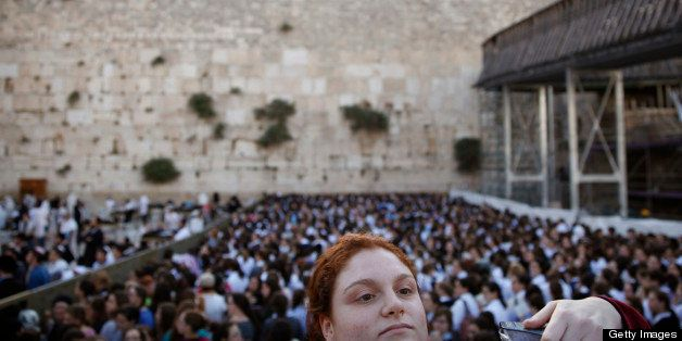 An Ultra Orthodox Jewish girl looks at members of the liberal eral Jewish religious group Women of the Wall on May 10, 2013 a