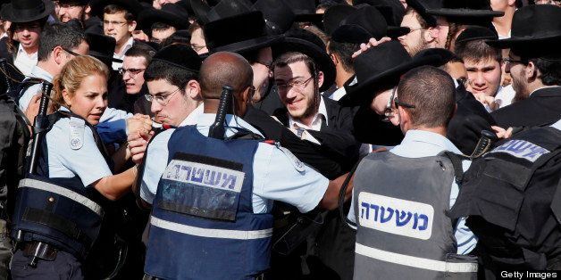 Israeli policemen push back a crowd of  Ultra Orthodox Jewish men during the monthly prayer of the liberal Jewish religious g