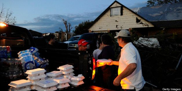 Derick Brock from Mercy Chefs distributes hot food to tornado victims at their devastated neighbourhood on May 21, 2013 in Mo