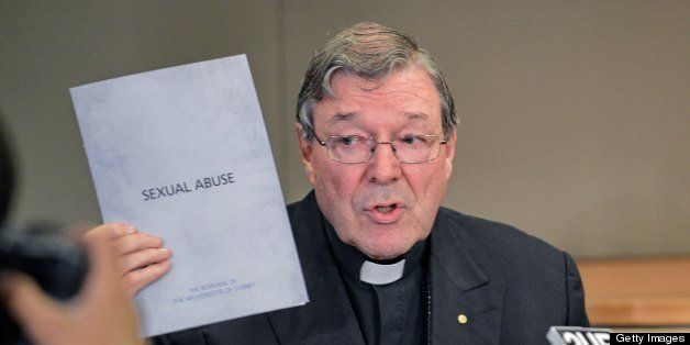 Sydney Archbishop Cardinal George Pell holds a document to the response of the archidiocese to sexual abuse during a press co