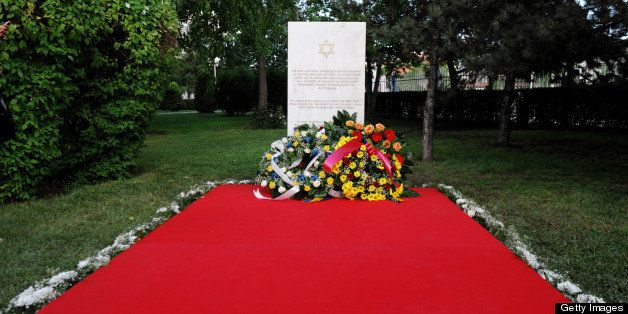 Flowers are placed in front of a plaque in Pristina on May 23, 2013, during an official ceremony of the Commemorative Plaque