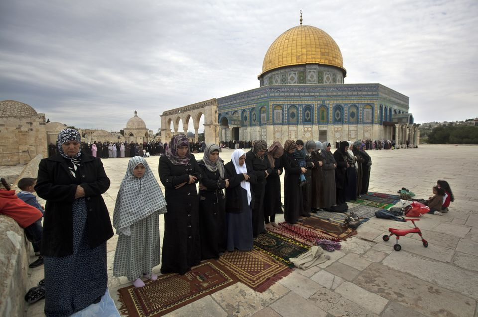 Palestinian women perform Friday prayers outside Jerusalem's Dome of the Rock, which is at the center of the Temple Mount, a