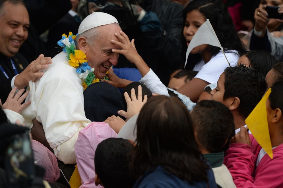Pope Francis is surrounded by children as he strolls around during his visit to the Varginha favela in Rio de Janeiro, on Jul