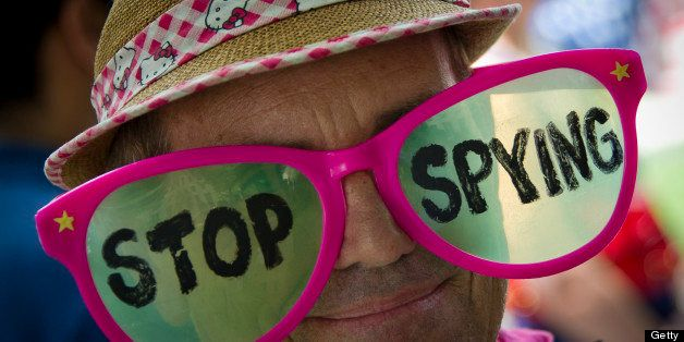 A human rights activists wears pink glasses reading 'stop spying' during a protest against the alleged violation of privacy b
