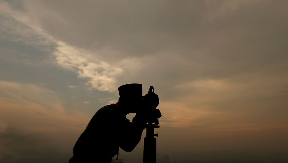 "An unidentified official of Malaysia's Islamic authority uses a telescope to perform ""Rukyah,"" the sighting of the new moon t"