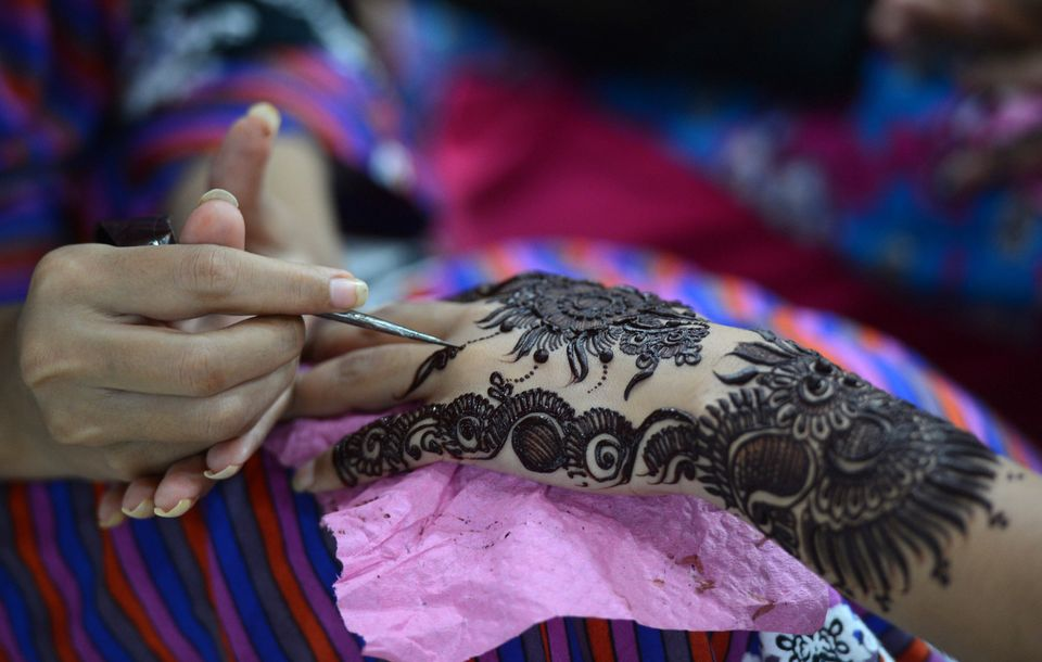 A Pakistani beautician applies traditional henna design to the hand of a customer ahead of the Muslim festivities of Eid al-F