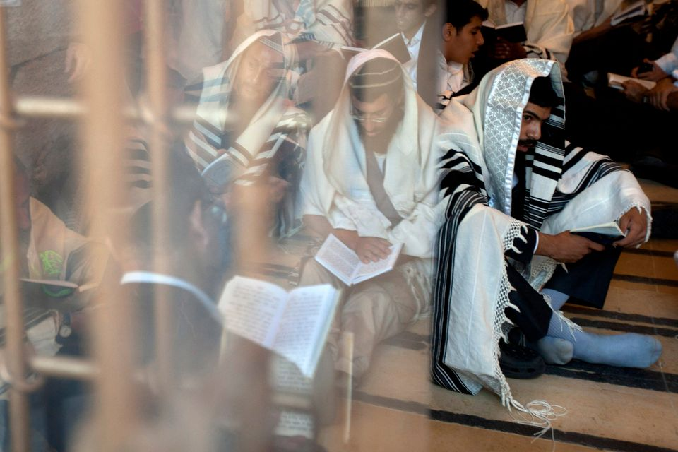 Ultra-Orthodox Jewish men pray as they gather for the mourning ritual of Tisha B'Av at the Western Wall, the holiest site whe