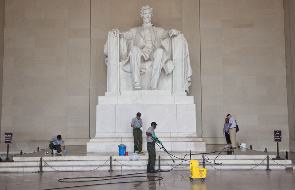 Workers with the National Park Service clean off paint thrown on the Lincoln Memorial overnight by vandals on the National Ma