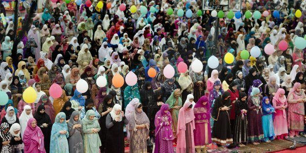Women gather behind the men during the Eid prayer, marking the end of Ramadan, the Muslim month-long fasting ritual as more t