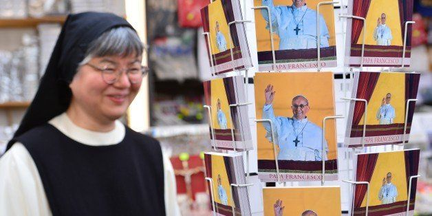 A nun looks at postcards of Pope Francis in a gift shop on March 15, 2013 near St Peter's square at the Vatican. Pope Francis