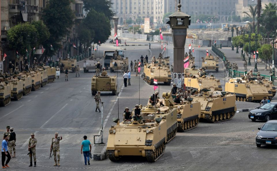 Egyptian army soldiers take their positions on top and next to their armored vehicles while guarding an entrance to Tahrir sq