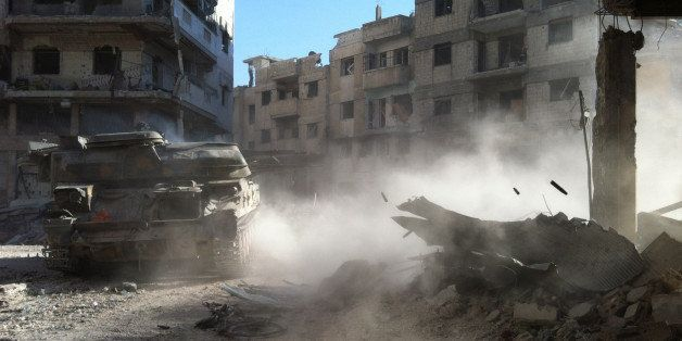 A Syrian government forces' tank rolls in the Khaldiyeh district of Syria's central city of Homs on July 28, 2013.  The Syria