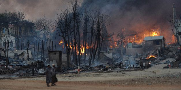Residents walk past buildings burning in riot-hit Meiktila, central Myanmar on March 21, 2013.  At least 10 people have been