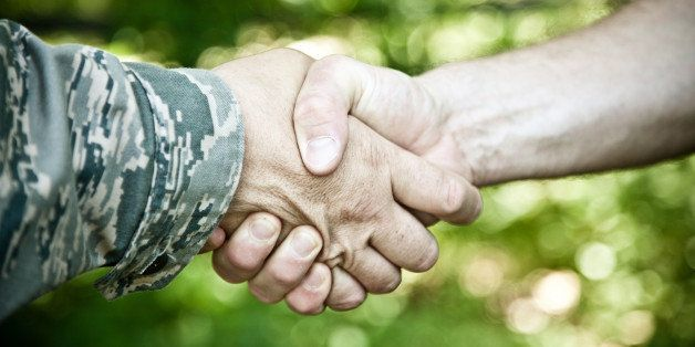 Military and civilian shake hands.