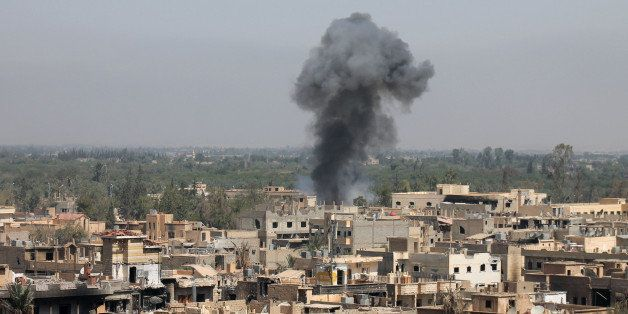 A photo taken on August 13, 2013 shows smoke billowing from buildings in Syria's eastern town of Deir Ezzor following an airs