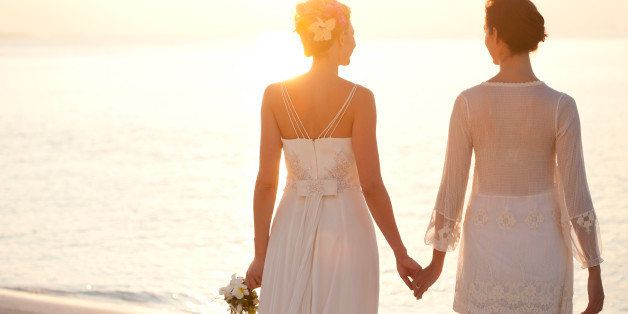 Same sex bridal couple holding hands at sunset