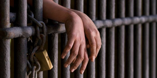 Close up of hands, behind the bars of a prison.