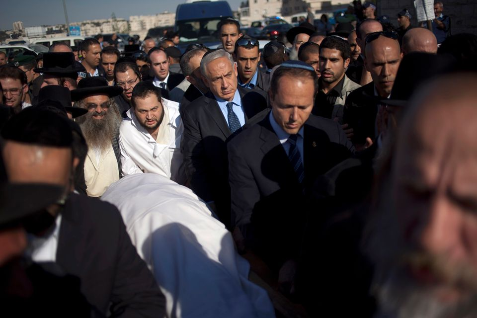 Israeli Prime Minister Benjamin Netanyahu, center, escorts the body of Rabbi Ovadia Yosef during his the funeral in Jerusalem