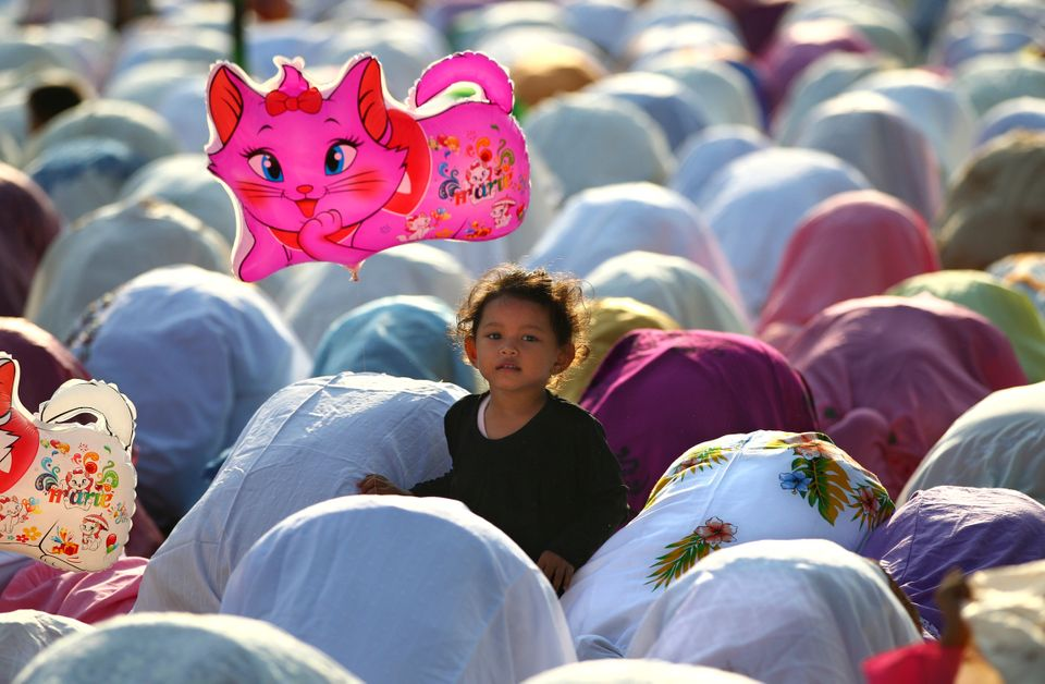 A Muslim girl holds a balloon during a morning prayer marking the Eid al-Adha holiday on a street in Jakarta, Indonesia, Tues