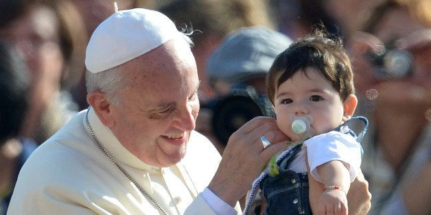 Pope Francis blesses a child as he arrives for his general audience at St Peter's square on October 16, 2013 at the Vatican.