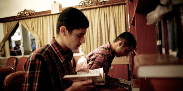 Iranian Jewish men read the holy Torah at a synagogue in downtown Tehran on September 24, 2013. Present for more than 2,500 y
