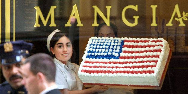 395293 01: A worker holds up an American flag cake at Mangia bakery in front of police officers standing guard during Preside
