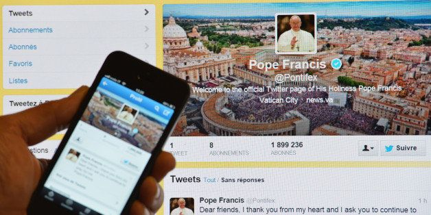 A man holds a smartphone showing Pope Francis' first tweet in front of a computer screen showing the same tweet on March 17,