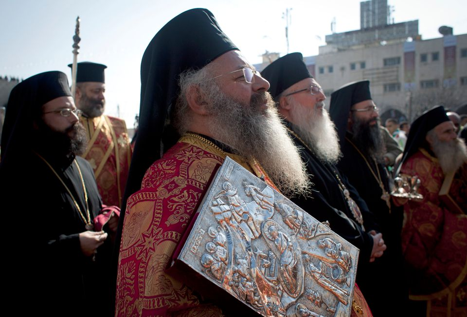 Greek Orthodox priests take part in the Christian Orthodox Christmas Eve celebrations at the Church of the Nativity, traditio