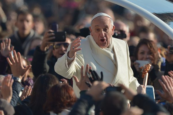 Pope Francis greets the crowd as he arrives for his general audience at St Peter's square on December 11, 2013 at the Vatican