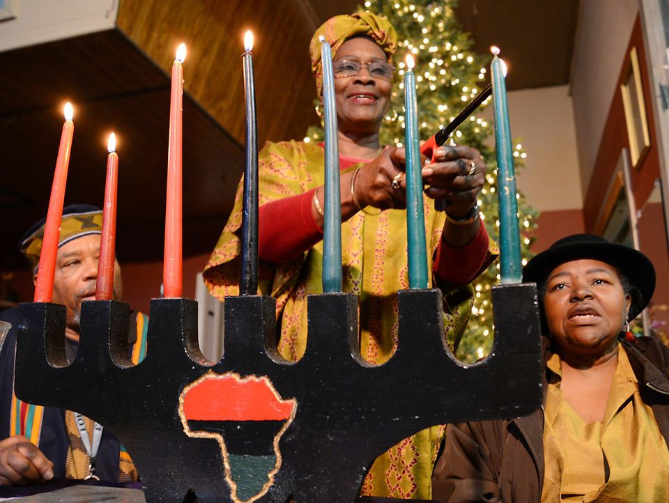 ADDS LAST SENTENCE - Travel Laguda, center, lights Kwanzaa candles on Friday, Dec. 28, 2012, at True Worship Outreach in Kins
