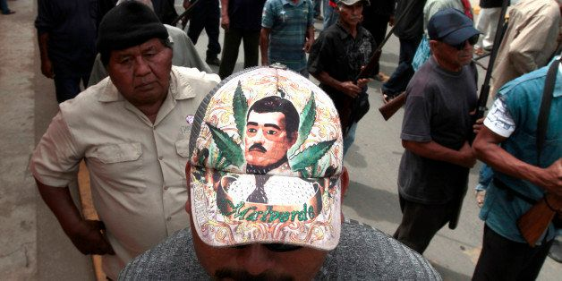 A community police member wearing a cap depicting Jesus Malverde --the saint of drug traffickers-- takes part in the March fo