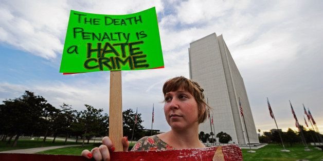 LOS ANGELES, CA - SEPTEMBER 28: Anti-death penalty protester Katie Wilde holds a placard during a rally and a march in front