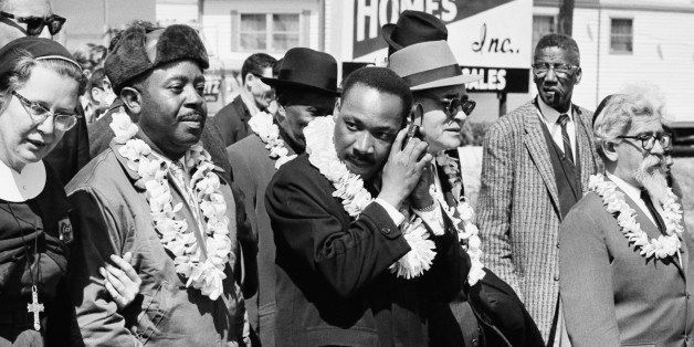 African-American civil rights activist Martin Luther King, Jr. (1929 - 1968, centre) listening to a transistor radio in the f