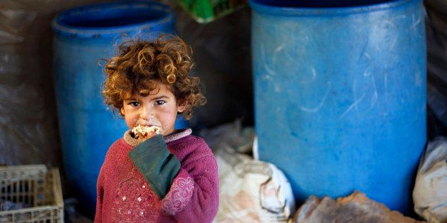 A young Palestinian Bedouin girl eats a peice of bread at their encampment in Khan Yunis in the southern Gaza Strip on Decemb