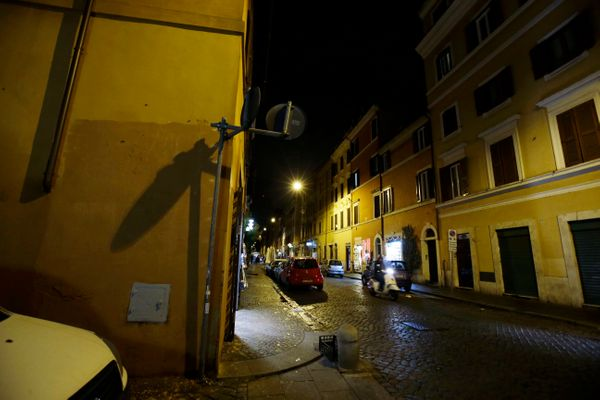 The wall, left, where the image depicting Pope Francis as Superman was posted, is seen empty at the Borgo Pio district near S