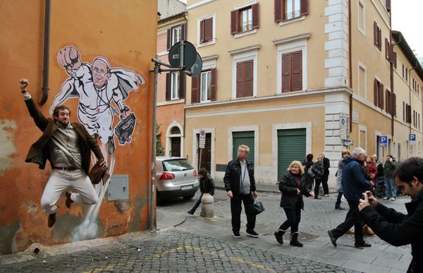 A tourist poses for a souvenir picture in front of a graffiti by Italian artist Mauro Pallotta depicting Pope Francis as Supe