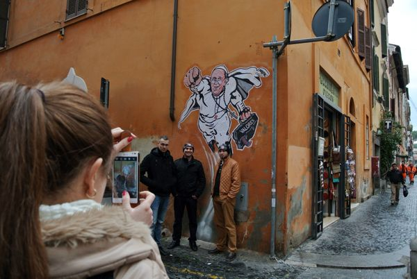 Tourists pose for a souvenir picture in front of a graffiti by Italian artist Mauro Pallotta depicting Pope Francis as Superm