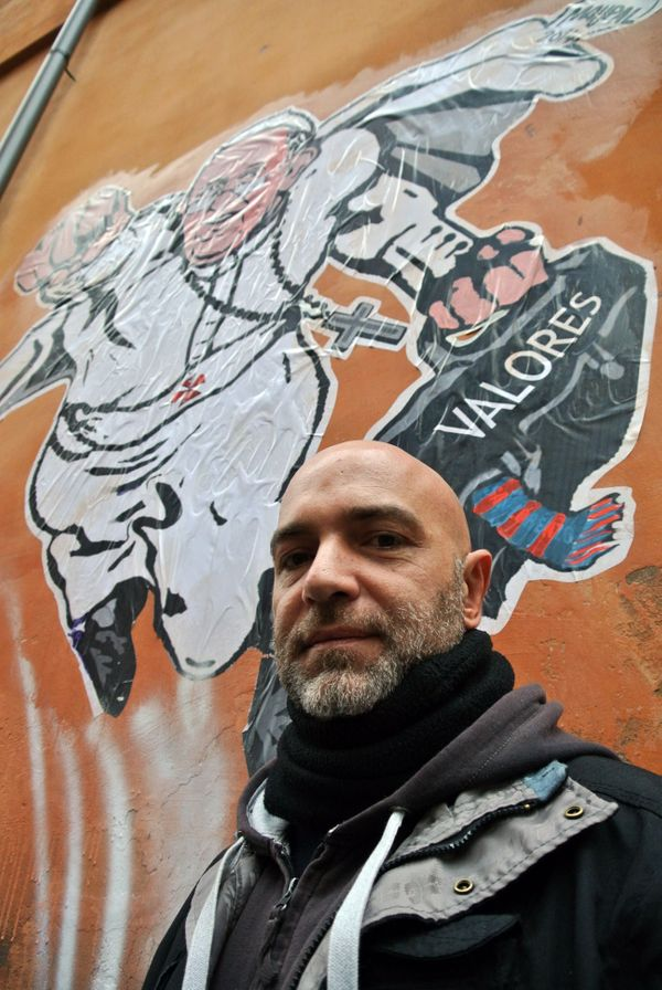 Italian artist Mauro Pallotta poses in front of his graffiti depicting Pope Francis as Superman. (AP Photo/Gregorio Borgia)