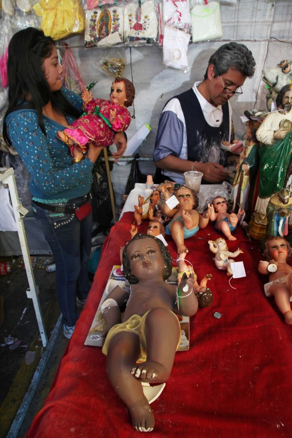 Jose Galvan, top right, and his daughter Gabriela restore statues of baby Jesus for clients at their stand outside a market i