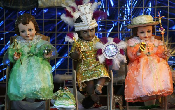 In this Saturday, Feb. 1, 2014 photo, statues of baby Jesus outfitted in different costumes are displayed for sale outside a