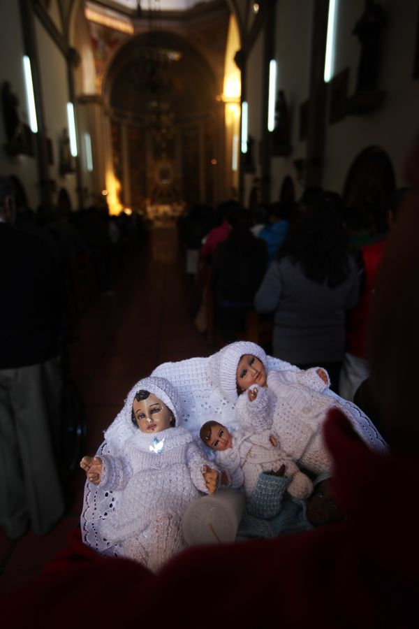 A parishioner holds her trio of baby Jesus statues inside the San Miguel Arcangel marking the Dia de Candelaria, or Day of Ca