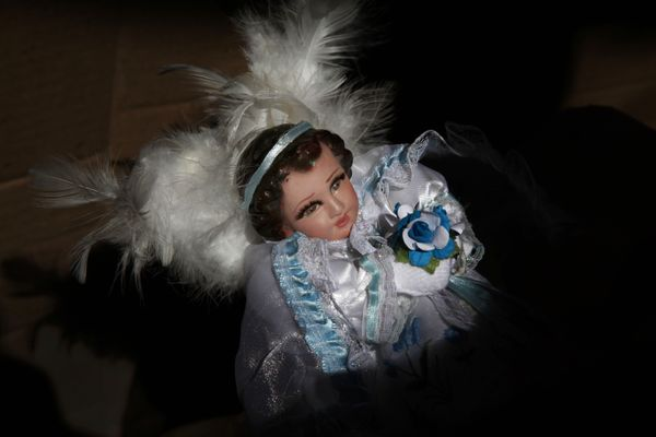 A figure of baby Jesus dressed as an angel is held by its owner at a stand that sells clothes for baby Jesus dolls in Mexico