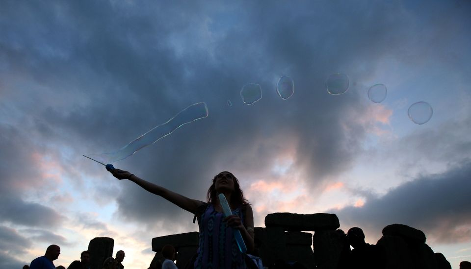 AMESBURY, ENGLAND - JUNE 20:  Robyn Smith makes bubbles as she waits for the arrival of the midsummer dawn at the megalithic