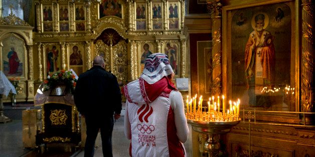 A Russian woman wearing a jacket of the Russian Olympic team prays inside St. Michael the Archangel Cathedral, Tuesday, Feb.