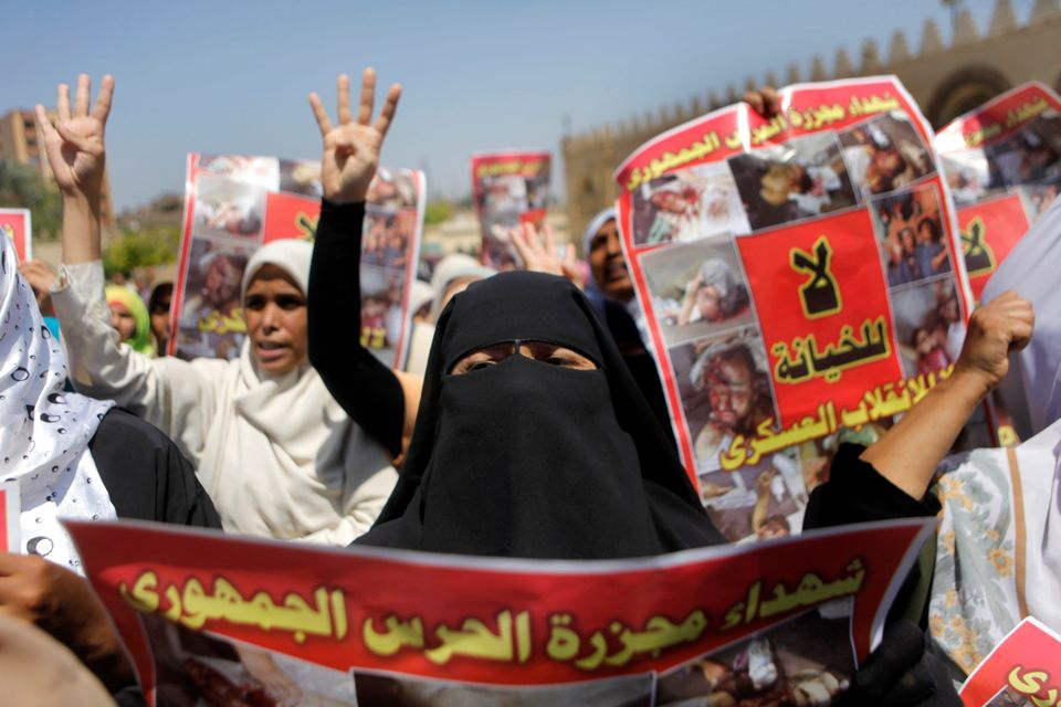 Supporters of Egypt's ousted President Mohammed Morsi hold posters showing victims of a military crackdown on their protest c