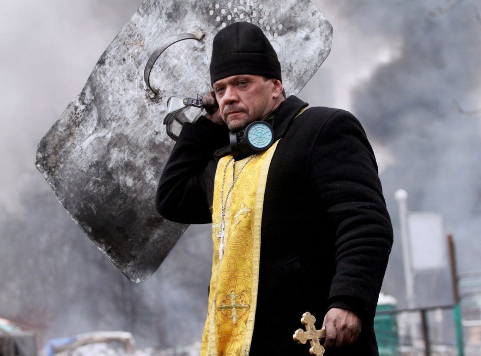 A priest holds a cross and shield during clashes between anti-government protesters and riot police in central Kiev on Februa