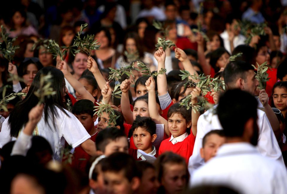 Iraqi Christian youth hold up olive branches as the gather at the St. Joseph church in Arbil, the capital of the autonomous K