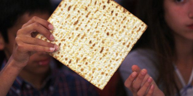 MIAMI BEACH, FL - MARCH 25:  Omri Brandes (L) and Nitzan Brandes eat matzo during a  community Passover Seder at Beth Israel