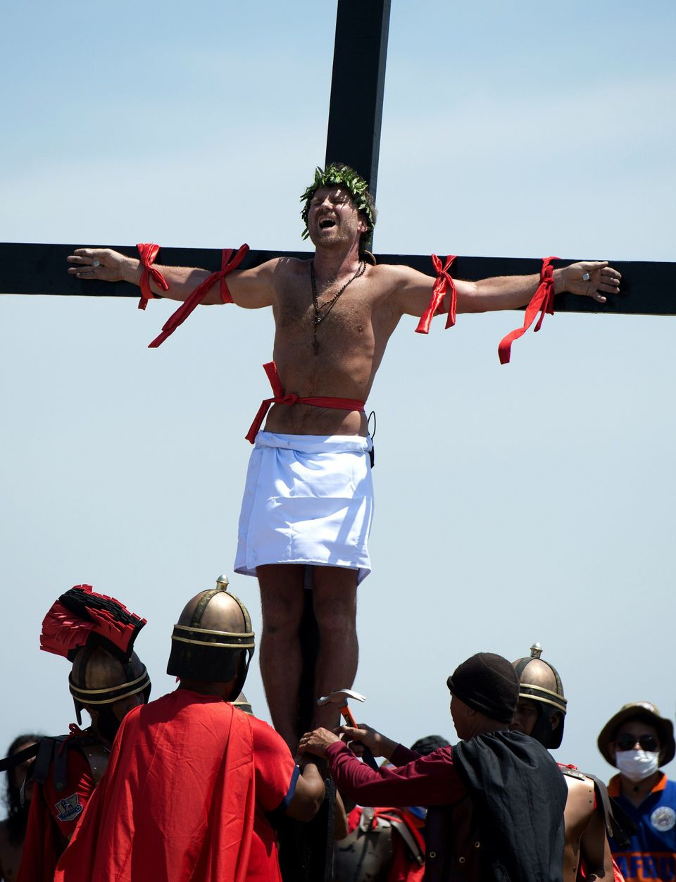 Danish film maker Lasse Spang Olsen grimaces as he is nailed to a cross during the a re-enactment of the Crucifixion of Chris