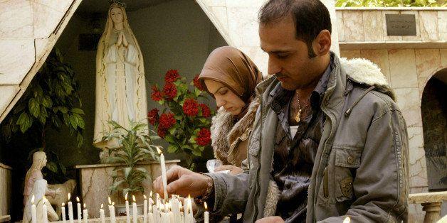 BAGHDAD, IRAQ, DECEMBER 25:  Iraqi Christians light candles after attending Christmas mass at the Virgin Mary church on Decem